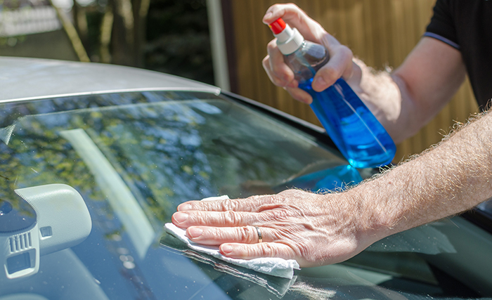 Man cleaning a car windshield